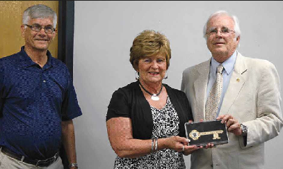 Alice Rouse, who recently retired as publisher of the Murray Ledger and Times, was presented a key to the city last week by Murray Mayor Bill Wells. At left is Alice's husband, Bill.