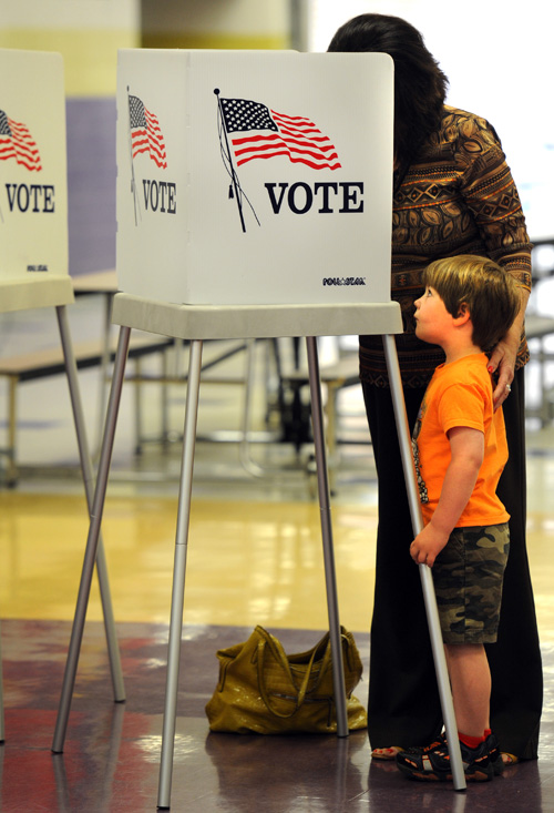 Bradley Knapp, 4, of Plum Springs, watches his grandmother, Myra Dwyer, of Bowling Green, vote Tuesday, May 20, 2014 at a percent at Bowling Green High School.Turnout at polling locations around Warren County is expected to be light today for the primary election. (AP Photo/Joe Imel, Daily News)
